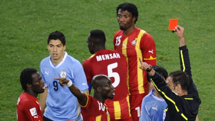 Uruguay's striker Luis Suarez (L) receiv