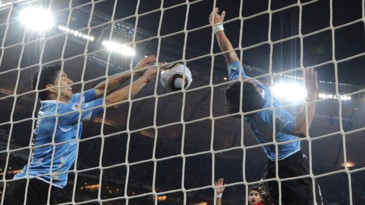 Uruguay's striker Luis Suarez (L) stops