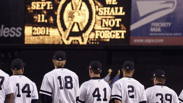 """BRONX, NY - SEPTEMBER 11:  On the one year anniversary of the tragic events of September 11, 2001, the New York Yankees sing the National Anthem with the scoreboard stating that """"We Shall Not Forget"""" on September 11, 2002 at Yankee Stadium in the Bronx, New York. The Yankees defeated the Orioles 5-4.  (Photo by Ezra Shaw/Getty Images)"""