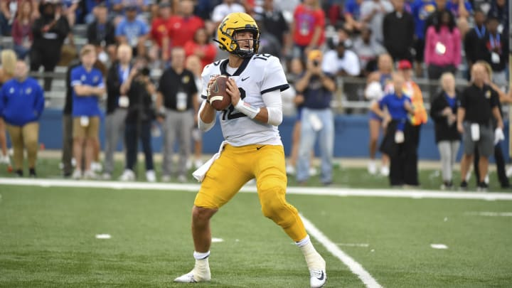 LAWRENCE, KS - SEPTEMBER 21: Quarterback Austin Kendall #12 of the West Virginia Mountaineers looks to pass against the Kansas Jayhawks at Memorial Stadium on September 21, 2019 in Lawrence, Kansas. (Photo by Ed Zurga/Getty Images)