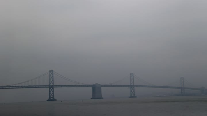 The San Francisco-Oakland Bay Bridge is seen through hazy and smoky conditions