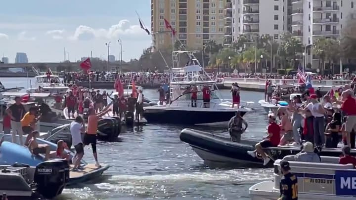 Tom Brady throws the Lombardi Trophy to another boat during Tampa Bay Buccaneers Super Bowl LV victory parade