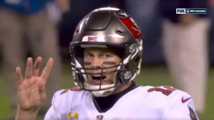 Tom Brady holding up four fingers.