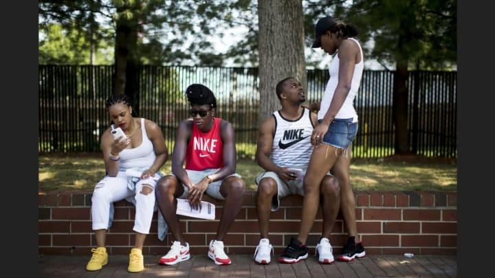 Brittany Boyd, Tina Charles, Avery Warley-Talbert and her husband rest on ledge at the amusement park.