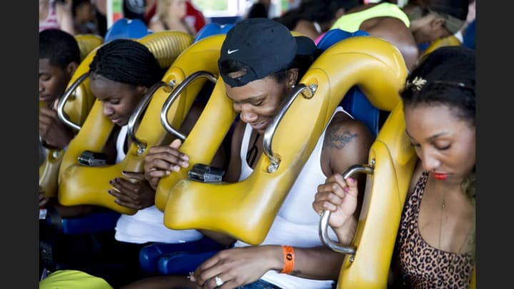 Avery Warley-Talbert buckles in to ride the roller coaster.
