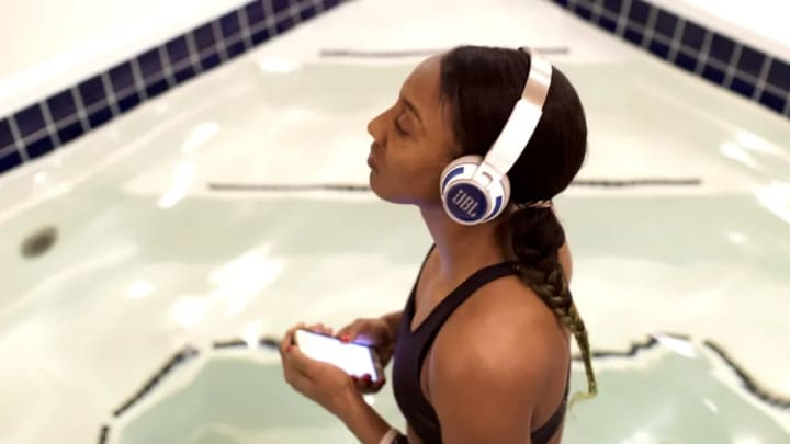 Candice Wiggins listens to her music while standing in the pool before the game.
