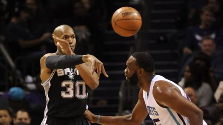 Mar 21, 2016; Charlotte, NC, USA; San Antonio Spurs forward David West (30) passes the ball as he is defended by Charlotte Hornets center Al Jefferson (25) during the first half of the game at Time Warner Cable Arena. Mandatory Credit: Sam Sharpe-USA TODAY Sports