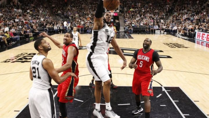 Mar 30, 2016; San Antonio, TX, USA; San Antonio Spurs power forward LaMarcus Aldridge (12) dunks the ball as New Orleans Pelicans center Kendrick Perkins (5) looks on during the second half at AT&T Center. The Spurs won 100-92. Mandatory Credit: Soobum Im-USA TODAY Sports