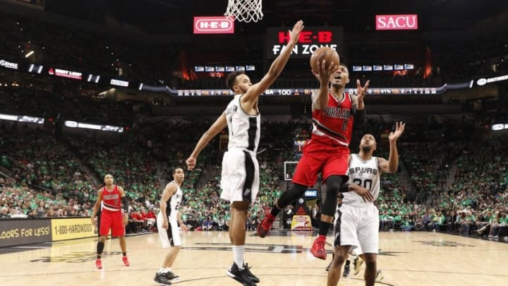 Mar 17, 2016; San Antonio, TX, USA; Portland Trail Blazers point guard Damian Lillard (0) shoots the ball past San Antonio Spurs small forward Kyle Anderson (1, left) and power forward David West (30, right) during the second half at AT&T Center. Mandatory Credit: Soobum Im-USA TODAY Sports