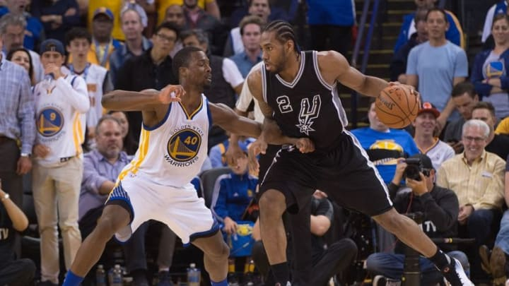 April 7, 2016; Oakland, CA, USA; San Antonio Spurs forward Kawhi Leonard (2) dribbles the basketball against Golden State Warriors forward Harrison Barnes (40) during the third quarter at Oracle Arena. The Warriors defeated the Spurs 112-101. Mandatory Credit: Kyle Terada-USA TODAY Sports