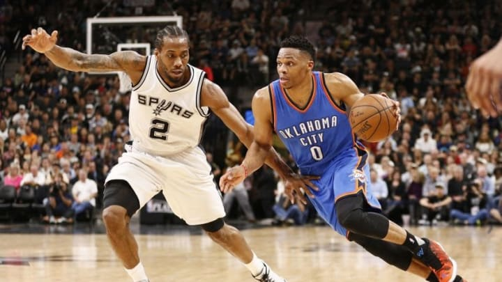 May 2, 2016; San Antonio, TX, USA; Oklahoma City Thunder point guard Russell Westbrook (0) dribbles the ball as San Antonio Spurs small forward Kawhi Leonard (2) defends in game two of the second round of the NBA Playoffs at AT&T Center. Mandatory Credit: Soobum Im-USA TODAY Sports