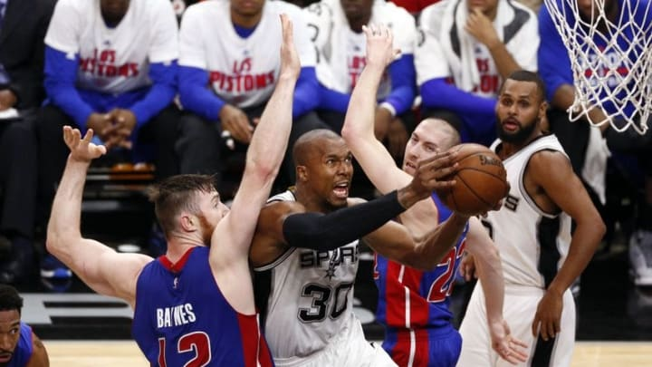 Mar 2, 2016; San Antonio, TX, USA; San Antonio Spurs power forward David West (30) drives for the basket between Detroit Pistons center Aron Baynes (12) and point guard Steve Blake (22) during the second half at AT&T Center. Mandatory Credit: Soobum Im-USA TODAY Sports