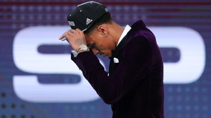Jun 23, 2016; New York, NY, USA; Dejounte Murray (Washington) puts on a team cap after being selected as the number twenty-nine overall pick to the San Antonio Spurs in the first round of the 2016 NBA Draft at Barclays Center. Mandatory Credit: Jerry Lai-USA TODAY Sports