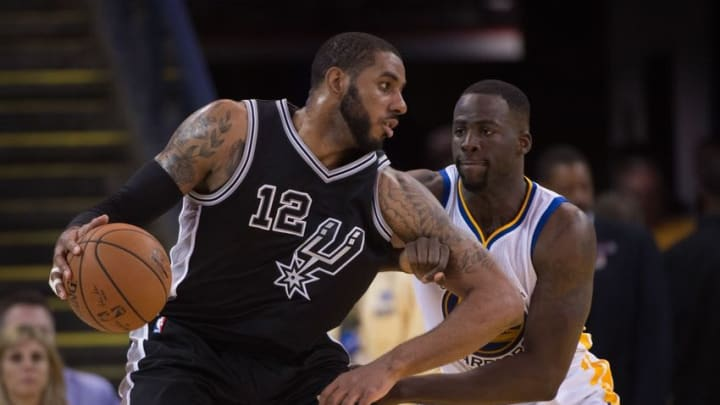 April 7, 2016; Oakland, CA, USA; San Antonio Spurs forward LaMarcus Aldridge (12) dribbles the basketball against Golden State Warriors forward Draymond Green (23) during the fourth quarter at Oracle Arena. The Warriors defeated the Spurs 112-101. Mandatory Credit: Kyle Terada-USA TODAY Sports