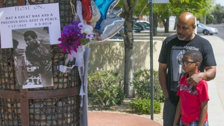 Jun 4, 2016; Scottsdale, AZ, USA: Lynn Boyd Jr. and his son Jayden Boyd look at an impromptu memorial for Muhammad Ali outside Scottsdale Osborne Medical Center. Mandatory Credit: Patrick Breen/The Arizona Republic via USA TODAY Network