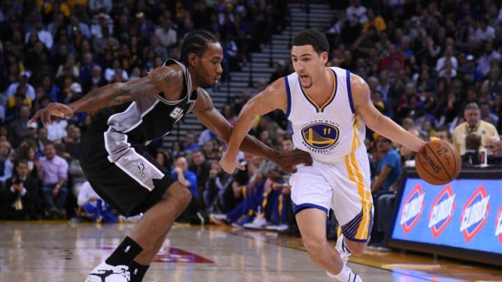 Nov 11, 2014; Oakland, CA, USA; Golden State Warriors guard Klay Thompson (11) dribbles the basketball against San Antonio Spurs forward Kawhi Leonard (2, left) during the first quarter at Oracle Arena. The Spurs defeated the Warriors 113-100. Mandatory Credit: Kyle Terada-USA TODAY Sports