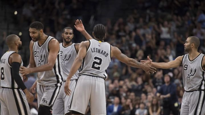 Apr 2, 2016; San Antonio, TX, USA; San Antonio Spurs guard Patty Mills (8) and center Tim Duncan (21) and forward LaMarcus Aldridge (12) and forward Kawhi Leonard (2) and guard Tony Parker (9) celebrate during the second half against the Toronto Raptors at the AT&T Center. The Spurs defeat the Raptors 102-95. Mandatory Credit: Jerome Miron-USA TODAY Sports