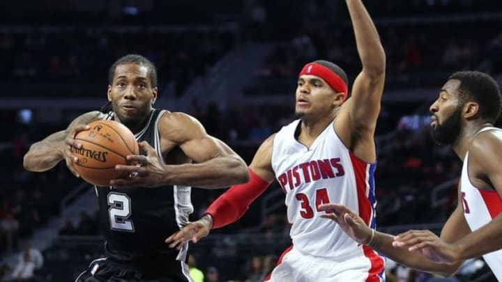 Oct 10, 2016; Auburn Hills, MI, USA; San Antonio Spurs forward Kawhi Leonard (2) prepares to shoot the ball as Detroit Pistons forward Tobias Harris (34) and center Andre Drummond (0) defend during the third quarter of the game at The Palace of Auburn Hills. The Spurs won 86-81. Mandatory Credit: Leon Halip-USA TODAY Sports