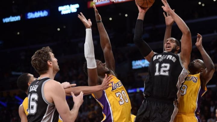 November 18, 2016; Los Angeles, CA, USA; San Antonio Spurs forward LaMarcus Aldridge (12) shoots to score a basket against the defense of Los Angeles Lakers forward Julius Randle (30) and forward Luol Deng (9) during the second half at Staples Center. Mandatory Credit: Gary A. Vasquez-USA TODAY Sports