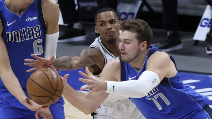 Apr 11, 2021; Dallas, Texas, USA; Dallas Mavericks guard Luka Doncic (77) and San Antonio Spurs guard Dejounte Murray (5) go for the ball during the