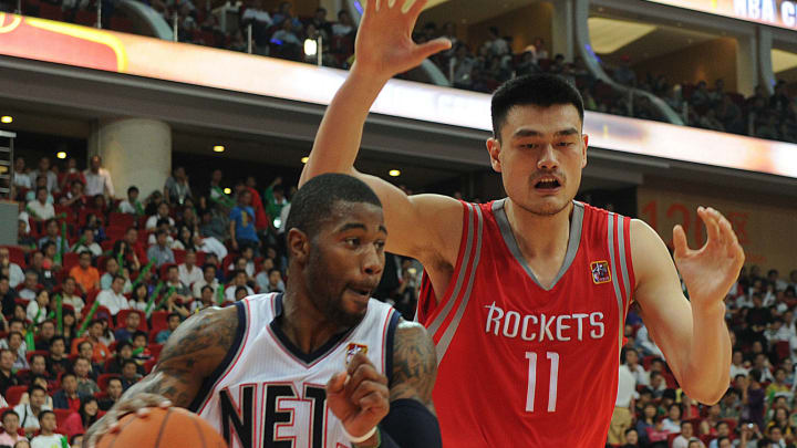 New Jersey Nets' Terrence Williams (L) dribbles past Houston Rockets' Yao Ming during the Houston Rockets and New Jersey Nets game in the NBA China Games 2010 at the International Sports Arena in Guangzhou on October 16, 2010. The Rockets and Nets are playing two exhibition games in China in Beijing and Guangzhou. AFP PHOTO/MIKE CLARKE (Photo credit should read MIKE CLARKE/AFP via Getty Images)