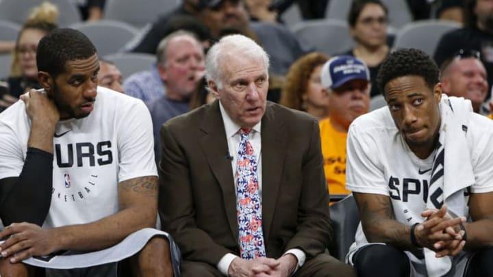SAN ANTONIO, TX - NOVEMBER 30: Gregg Popovich head coach of the San Antonio Spurs talks with players LaMarcus Aldridge #12, and DeMar DeRozan #10 on the bench (Photo by Edward A. Ornelas/Getty Images)