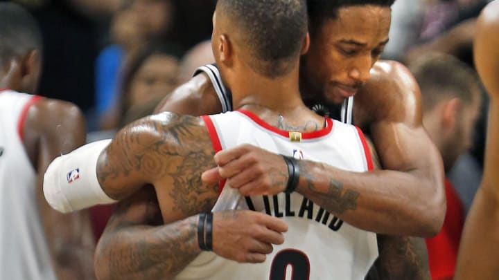 SAN ANTONIO, TX – DECEMBER 2: DeMar DeRozan #10 of the San Antonio Spurs hugs Damian Lillard #0 of the Portland Trail Blazers at the end of the game at AT&T Center on December 2nd. Photo by Ronald Cortes/Getty Images)