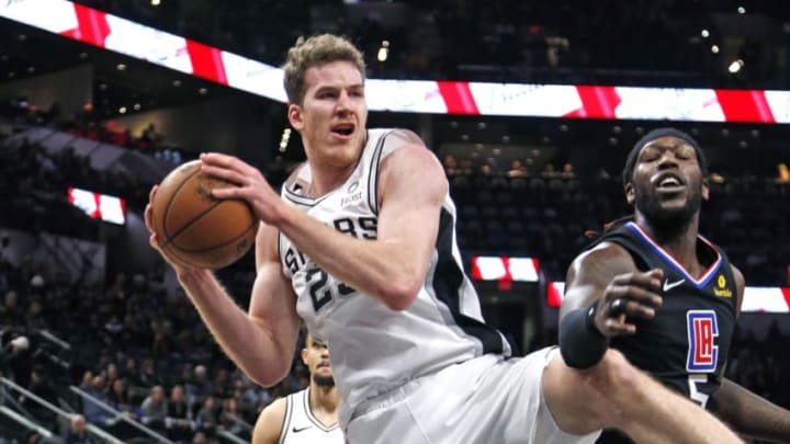 SAN ANTONIO, TX - DECEMBER 13: Jakob Poeltl #25 of the San Antonio Spurs grabs a rebound next to Montrezl Harrell #5 of the Los Angeles Clippers at AT&T Center on December 13, 2018 in San Antonio, Texas. NOTE TO USER: User expressly acknowledges and agrees that , by downloading and or using this photograph, User is consenting to the terms and conditions of the Getty Images License Agreement. (Photo by Ronald Cortes/Getty Images)