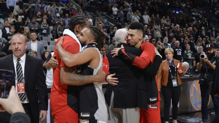 SAN ANTONIO, TX - JANUARY 3: Kawhi Leonard #2 of the Toronto Raptors Patty Mills #8 of the San Antonio Spurs Head Coach Gregg Popovich of the San Antonio Spurs and Danny Green #14 of the Toronto Raptors exchange hugs after the game on January 3, 2019 at the AT&T Center in San Antonio, Texas. NOTE TO USER: User expressly acknowledges and agrees that, by downloading and or using this photograph, user is consenting to the terms and conditions of the Getty Images License Agreement. Mandatory Copyright Notice: Copyright 2019 NBAE (Photos by Mark Sobhani/NBAE via Getty Images)