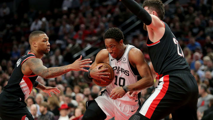 PORTLAND, OR – FEBRUARY 07: DeMar DeRozan #10 of the San Antonio Spurs works against Damian Lillard #0 (L) and Jusuf Nurkic #27 of the Portland Trail Blazers in the first quarter during their game at Moda Center. (Photo by Abbie Parr/Getty Images)