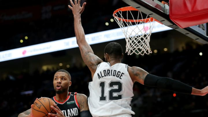 PORTLAND, OR - FEBRUARY 07: Damian Lillard #0 of the Portland Trail Blazers looks to pass the ball against LaMarcus Aldridge #12 of the San Antonio Spurs in the fourth quarter during their game at Moda Center on February 7, 2019 in Portland, Oregon. NOTE TO USER: User expressly acknowledges and agrees that, by downloading and or using this photograph, User is consenting to the terms and conditions of the Getty Images License Agreement. (Photo by Abbie Parr/Getty Images)