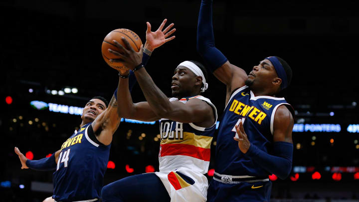 NEW ORLEANS, LOUISIANA – JANUARY 30: Jrue Holiday #11 of the New Orleans Pelicans drives against Gary Harris #14 of the Denver Nuggets and Paul Millsap #4 during the first half at the Smoothie King Center on January 30, 2019 in New Orleans, Louisiana. (Photo by Jonathan Bachman/Getty Images)