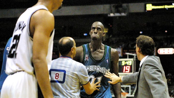 Kevin Garnett of the Minnesota Timberwolves (C) has to be restrained by referree Luis Grillo (8) and head coach Flip Saunders (R) after he and Tim Duncan of the San Antonio Spurs (L) almost come to blows. (Photo credit should read PAUL BUCK/AFP via Getty Images)