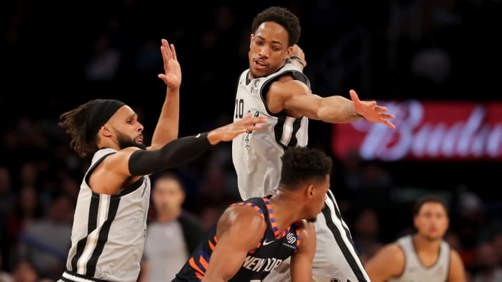 NEW YORK, NEW YORK – FEBRUARY 24: Dennis Smith Jr. #5 of the New York Knicks tries to get around Patty Mills #8 and DeMar DeRozan #10 of the San Antonio Spurs at Madison Square Garden on February 24, 2019 in New York City.The New York Knicks defeated the San Antonio Spurs 130-118. (Photo by Elsa/Getty Images)
