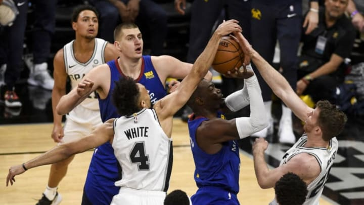 SAN ANTONIO, TX - APRIL 20: Jakob Poeltl (25) of the San Antonio Spurs and Derrick White (4) defend Paul Millsap (4) of the Denver Nuggets during the first quarter on Saturday, April 20, 2019. The Denver Nuggets and the San Antonio Spurs faced off for game four of their first round NBA playoffs series at the At&T Center. (Photo by AAron Ontiveroz/MediaNews Group/The Denver Post via Getty Images)