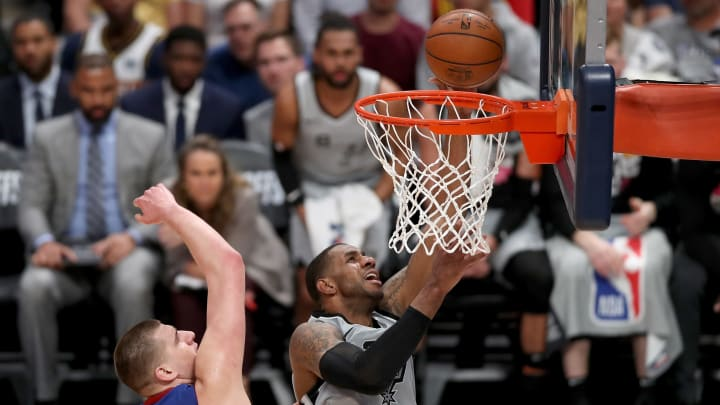 DENVER, COLORADO – APRIL 23: Lamarcus Aldridge #12 of the San Antonio Spurs goes to the basket against Nikola Jokic #15 of the Denver Nuggets in the second quarter of Game Five (Photo by Matthew Stockman/Getty Images)