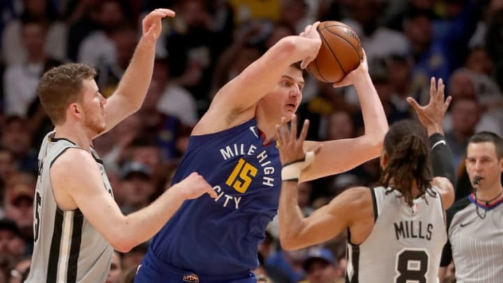 Nikola Jokic is guarded by Jakob Poeltl and Patty Mills of the San Antonio Spurs (Photo by Matthew Stockman/Getty Images)
