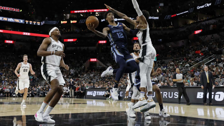 SAN ANTONIO, TX – OCTOBER 18: Ja Morant #12 of the Memphis Grizzlies shoots around Dejounte Murray #5 of the San Antonio Spurs as Rudy Gay #22 moves in on the play. (Photo by Edward A. Ornelas/Getty Images)