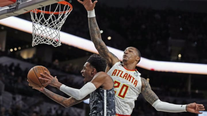 Dejounte Murray #5 of the San Antonio Spurs attempts an acrobatic layup contested by John Collins #20 of the Atlanta Hawks (Photo by Ronald Cortes/Getty Images)