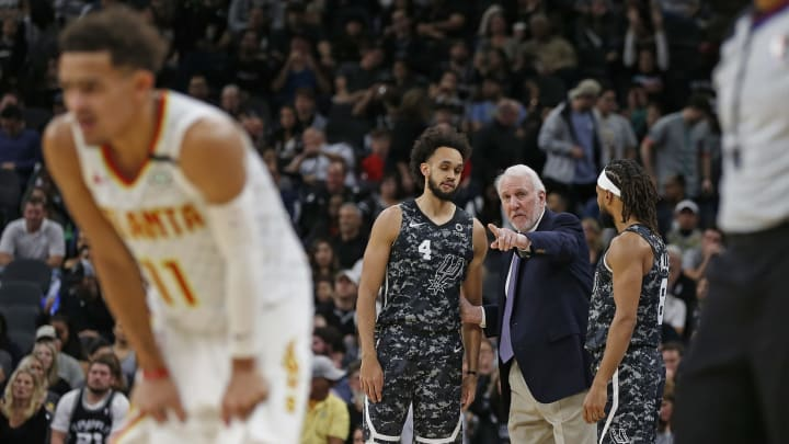 SAN ANTONIO, TX – JANUARY 17: Derrick White #4 of the San Antonio Spurs and Patty Mills #8 listen to hear coach Gregg Popovich during second half action at AT&T Center (Photo by Ronald Cortes/Getty Images)