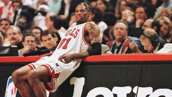 Dennis Rodman of the Chicago Bulls leans on the scorers table as he waits to come into the game against the Utah Jazz 10 June in game four of the NBA Finals at the United Center in Chicago, IL. Rodman hit four free throws down the stretch to lead the Bulls as they beat the Jazz 86-82 to lead the best-of-seven series 3-1. AFP PHOTO/Jeff HAYNES (Photo by JEFF HAYNES / AFP) (Photo by JEFF HAYNES/AFP via Getty Images)