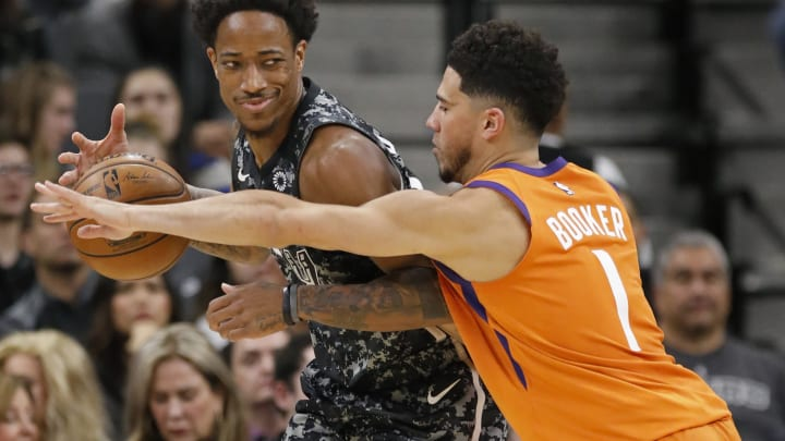 SAN ANTONIO, TX – JANUARY 24: DeMar DeRozan #10 of the San Antonio Spurs looks for room around Devin Booker #1 of the Phoenix Suns during an NBA game at the AT&T Center. (Photo by Edward A. Ornelas/Getty Images)