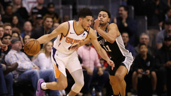 PHOENIX, ARIZONA - JANUARY 20: Devin Booker #1 of the Phoenix Suns handles the ball against Bryn Forbes #11 of the San Antonio Spurs during the NBA game at Talking Stick Resort Arena (Photo by Christian Petersen/Getty Images)