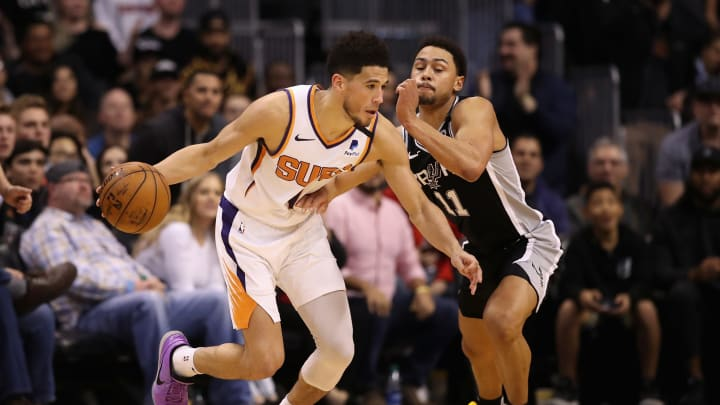 PHOENIX, ARIZONA – JANUARY 20: Devin Booker #1 of the Phoenix Suns handles the ball against Bryn Forbes #11 of the San Antonio Spurs during the NBA game at Talking Stick Resort Arena (Photo by Christian Petersen/Getty Images)