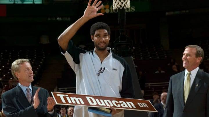 Tim Duncan acknowledges the crowd after Winston-Salem mayor Allen Joines (L) and Wake Forest Athletic Director Ron Wellman presented him with a street sign to commemorate Tim Duncan Drive at the LJVM Coliseum in Winston-Salem, NC, October 13, 2005. (Photo by Brian A. Westerholt/Getty Images)