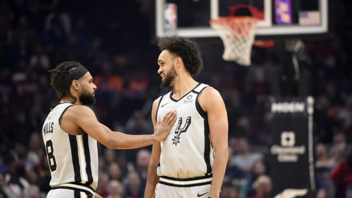 CLEVELAND, OHIO – MARCH 08: Patty Mills #8 talks to Derrick White #4 of the San Antonio Spurs during the first half against the Cleveland Cavaliers at Rocket Mortgage Fieldhouse (Photo by Jason Miller/Getty Images)