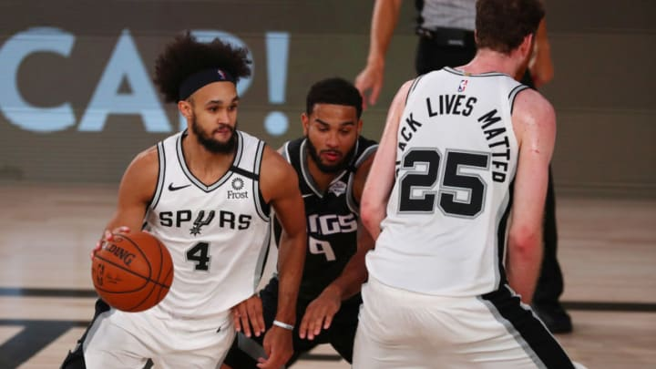 LAKE BUENA VISTA, FLORIDA - JULY 31: Derrick White #4 of the San Antonio Spurs controls the ball against the Sacramento Kings in the second half of an NBA basketball game at the Visa Athletic Center in the ESPN Wide World Of Sports Complex on July 31, 2020 in Lake Buena Vista, Florida. NOTE TO USER: User expressly acknowledges and agrees that, by downloading and or using this photograph, User is consenting to the terms and conditions of the Getty Images License Agreement. (Photo by Kim Klement - Pool/Getty Images)