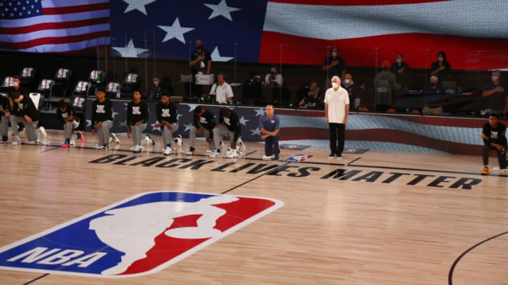 LAKE BUENA VISTA, FLORIDA - AUGUST 05: Members of the Denver Nuggets, concluding head coach Michael Malone, kneel as San Antonio Spurs head coach Gregg Popovich (middle) stands for the National Anthem before a game in the NBA Bubble at HP Field House at ESPN Wide World Of Sports Complex on August 5, 2020 in Lake Buena Vista, Florida. (Photo by Kim Klement-Pool/Getty Images)