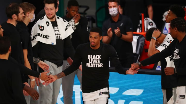 LAKE BUENA VISTA, FLORIDA – AUGUST 05: San Antonio Spurs guard Dejounte Murray #5 is greeted by teammates during player introductions before an NBA game at HP Field House. (Photo by Kim Klement-Pool/Getty Images)