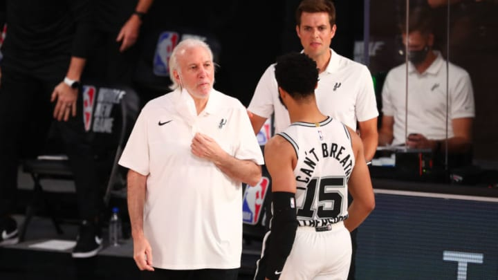 LAKE BUENA VISTA, FLORIDA - AUGUST 05: Head coach Gregg Popovich of the San Antonio Spurs talks with Quinndary Weatherspoon #15 during action against the Denver Nuggets in the second half at Visa Athletic Center at ESPN Wide World Of Sports Complex on August 5, 2020 in Lake Buena Vista, Florida. NOTE TO USER: User expressly acknowledges and agrees that, by downloading and or using this photograph, User is consenting to the terms and conditions of the Getty Images License Agreement. (Photo by Kim Klement-Pool/Getty Images)